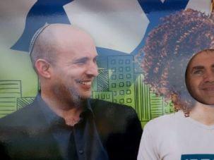 He's the Man: A Jewish settler in the West Bank poses for photo next to life-sized poster of far right leader Naftali Bennett.