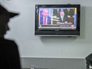 Israelis watch Benjamin Netanyahu's speech at a cafe in Tel Aviv.