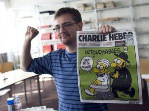 Free Speech? An editor shows 2012 front page of French satire magazine with cartoon depicting a Jew and the Prophet Muhammed.