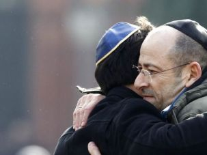 Mourners embrace at memorial service for Dan Uzan, the Jewish guard killed in Copenhagen terror attacks.