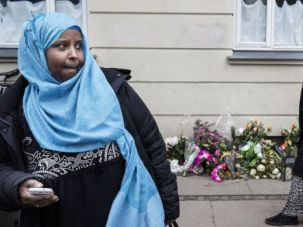 Muslim women walk by flowers left at site where suspected terrorist gunman was killed by Copenhagen police.