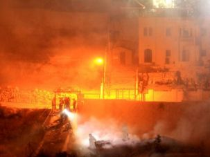 Heat in Hebron: Smoke billows above what remains of the house of Hussam Qawasmeh, who has now been charged by Israel for organizing the murder of three kidnapped Israeli teens, after the Israeli army demolished it with explosives.