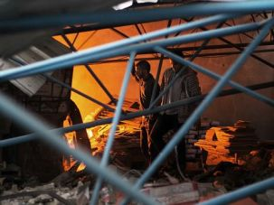 Gaza Burning: Gaza firefighters try to douse flames after Israeli air strikes hit a factory.