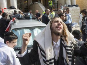 Israeli man mourns the killings at a synagogue in the Har Nof section of Jerusalem.