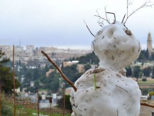 Holy Frosty: A scrawny melting snowman stands sentry over the Old City of Jerusalem as a nasty winter storm eased.