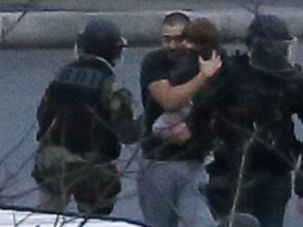 Police comfort a child among the hostages freed from a siege at a Paris kosher grocery.