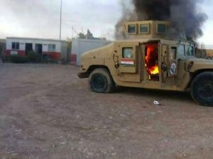 An armoured vehicle belonging to Iraqi security forces is in flames after hundreds of militants from the Islamic State launched a major assault on the security forces in Mosul.