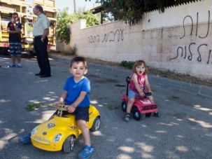 Getty images Not the Norm: Israeli Arab children play next to wall daubed with racist graffiti. Hate crimes grab headlines but a new study suggests that Jewish attitudes towards Arabs have moderated slightly over time.