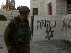 Israeli soldier walks past a mosque that was attacked by suspected Jewish extremists on the occupied West Bank.