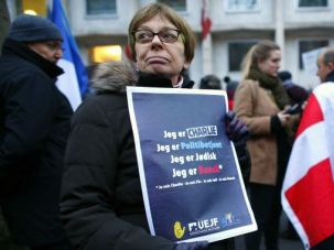 United in Grief: A protester holds a newspaper reading in Danish 'I am Charlie. I am a police officer. I am Jewish. I am Danish' during a demonstration.