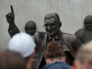 Hero No More: Fans pose with iconic bronze statue of Joe Paterno, the late scandal-tarred football coach of Penn State. Hours later, workers removed the statue in response to revelations about Paterno?s central role in a cover up of sex abuse.