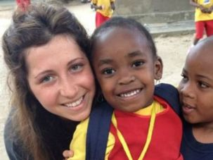 Happier Days: Kirstie Trup poses with children at a school in Zanzibar where she was volunteering before a horrifying acid attack.