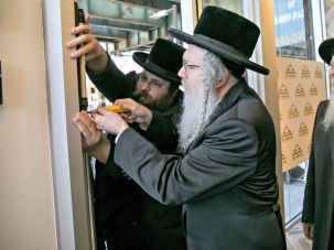 Affixing the mezuzah at the door of the new Boro Park location are Masbia Executive Director Alexander Rapaport (left), Rabbi Isaac Tirnauer of Shomrei Shabbos (center) and Rabbi Abraham Friedlander.