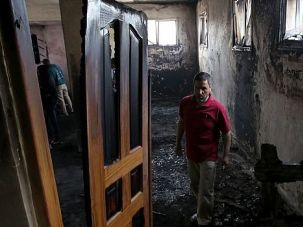 Hate Crime: A Palestinian man stands inside a mosque that was set ablaze by Israeli settlers in al-Mughayir, in the occupied West Bank near the Jewish settlement of Shilo.