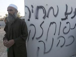 Hate Crime: Muslim clerics stand next to anti-Arab graffiti scrawled outside a West Bank mosque that was firebombed by Jewish exremists.