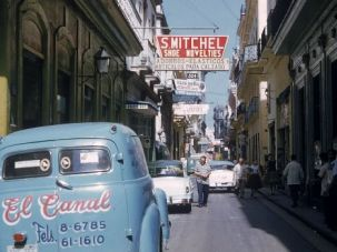 Cars are parked along a narrow street as pedestrians walk in downtown Havana in the 1950s.