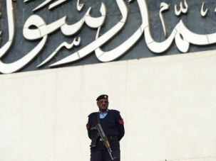 Worlds Apart: A Pakistani policeman stands guard at the Parliament as it passed a symbolic resolution condemning Charlie Hebdo's caricatures of the Prophet Muhammed as 'blasphemous.'