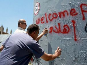 Welcome to Palestine: Palestinians spraypaint a welcome for Pope Francis on an Israeli military watchtower on the separation barrier in Bethlehem.