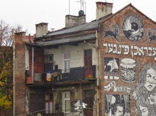 Street Art: Near the Jewish quarter in Krakow is this building covered with Art Deco-style graffiti. It says 'broken finger' in Yiddish.