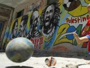 Kicking It Up a Notch: A Palestinian boy kicks a ball in front of graffiti wall murals depicting Portugal's football player Cristiano Ronaldo.