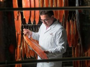 Lance Anisfeld, here inspecting smoked salmon, is commonly known as Lance Forman to match the name of the family-founded company he heads.