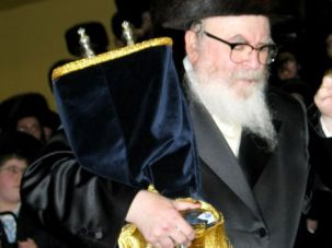 Rabbi David Twersky holds a Torah scroll.