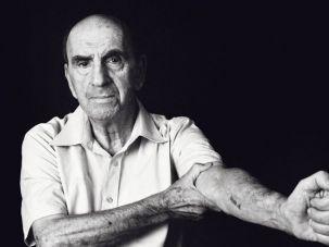 A Holocaust survivor displays tattoo Nazis inked on his arm.
