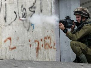 Rising Toll: Israeli soldiers fire tear gas at Palestinian demonstrators in Hebron on the occupied West Bank, where killings of Palestinians tripled in 2013. The first victim of 2014 was an 85-year-old man.