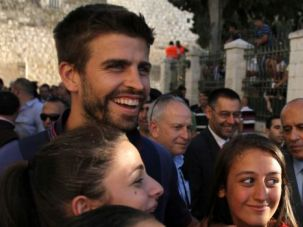 Universal Language: Barcelona star Gerald Pique poses with Palestinian teenagers during visit to West Bank.