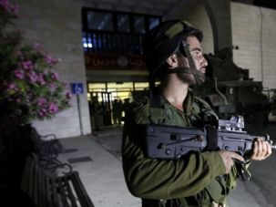 Crackdown WIdens: Israeli soldier stands guard at entrance to Bir Zeit University, where troops raided a student group that supports Hamas.