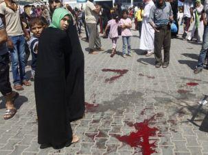Rising Toll: Palestinians walk by trail of blood near desks as a Gaza school hit by Israeli shelling.