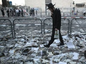 Change Is Coming: An ultra-Orthodox man walks past discarded election pamphlets in Jerusalem. A small but growing number of Haredi Jews are seeking to enter modern life by getting jobs and even joining the military. Some women are even running for offfice.
