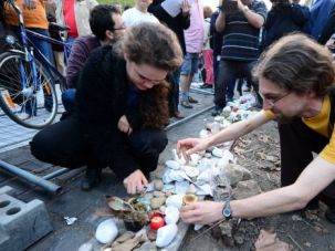 Protest and Mourning: Demonstrators light candles at a Jewish memorial stone of the Holocaust victims as participants pull down a mental fence around a planned memorial of the Nazi occupation of Hungary.