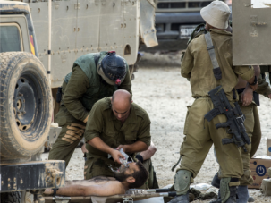 Wounded Comrade: Israeli soldiers evacuate fellow soldier injured in Gaza fighting.