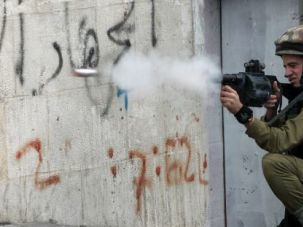 Rising Toll: Israeli soldiers fire tear gas at Palestinian demonstrators in Hebron on the occupied West Bank, where killings of Palestinians tripled in 2013.