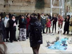 Women light menorah at the Kotel.