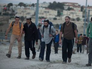 Build Baby Build: Israeli settlers march to claim a portion of the West Bank near their settlement. Government figures show Israel is accelerating construction in the occupied territory.