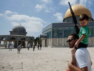 Disputed Place: Palestinian boy holds a toy gun as he rides on his father?s shoulders on the Temple Mount in Jerusalem.