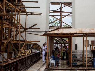Praying for Help: Filipino survivors of Typhoon Haiyan worship in damaged church.