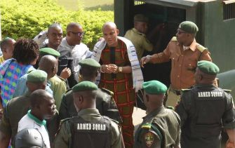 IPOB leader Nnamdi Kanu, hand-cuffed at center, is draped in a prayer shawl as armed state forces surround him.