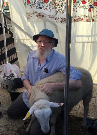 Temple activist Yehuda Etzion holds on to the lamb before the slaughter.