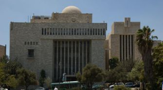 Keeper: The Torah was donated to Hechal Shlomo, the building at left, with the understanding that it would be housed in the Great Synagogue, on the right.