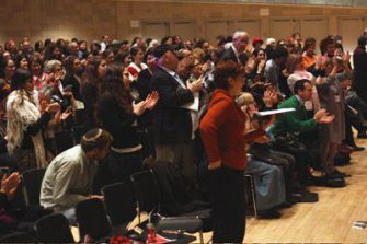 Respect: The audience rises to its feet as Sara Hurwitz delivers the plenary speech at JOFA.