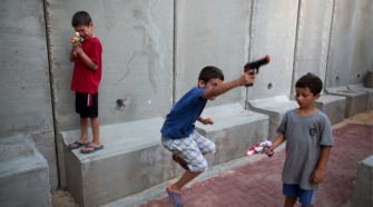 War Games:  Israeli children in Kibbutz Nahal Oz near the Gaza border play with toy guns next to a newly built concrete protection wall around their kindergarten.