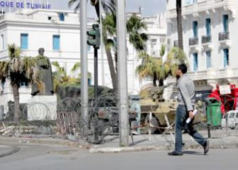A man walks past a tank and armor vehicle surrounded by razor wire in downtown Tunis.