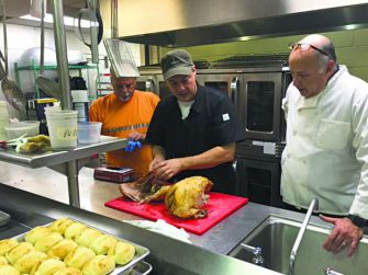 Camp Cut-Ups: Todd Jones, Ramah Darom's executive chef, instructs volunteers Dan Siegler (left) and Bruce Goldstein on cutting turkeys for the Thanksgiving meal.