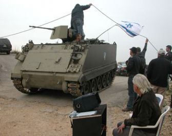 Action: Syrian director Najdat Anzour, seated, looks on as the cast and crew of ?The Living Martyr? prepare for a scene.