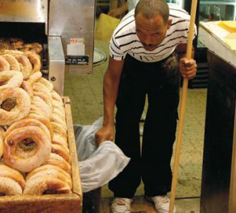 Destination: At Tel Aviv?s Central Bus Station an African worker sweeps up after hours in a pizzeria.