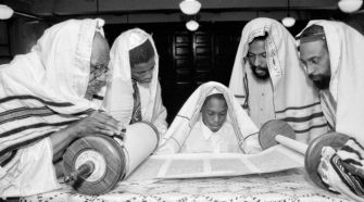 Rabbi Paris, left, examines a Torah scroll with other black Jewish leaders and a young student.