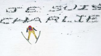 A skier jumps over a solidarity message for the victims of the Paris terror attack at the Nordic Combined World Cup in the French Alps town of Chaux-Neuve.